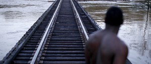 A man stands on a railway bridge to check the level of a flooded river.