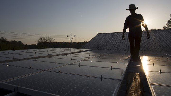 A person wearing a cowboy hat walks along a row of solar panels.