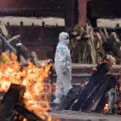 A man wearing protective equipment stands among burning pyres.