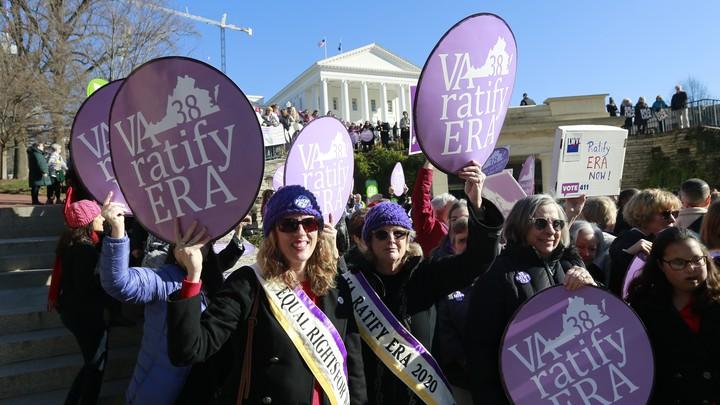"Equal Rights Amendment supporters holding up ""VA 38 ratify ERA"" signs"