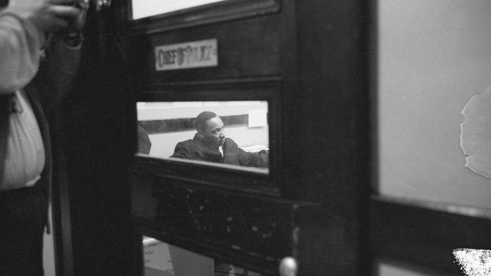 Martin Luther King Jr., seen through a small window in a door