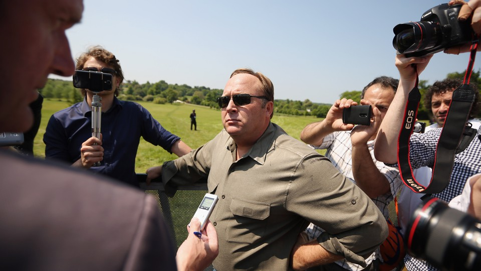 Alex Jones surrounded by people holding cameras