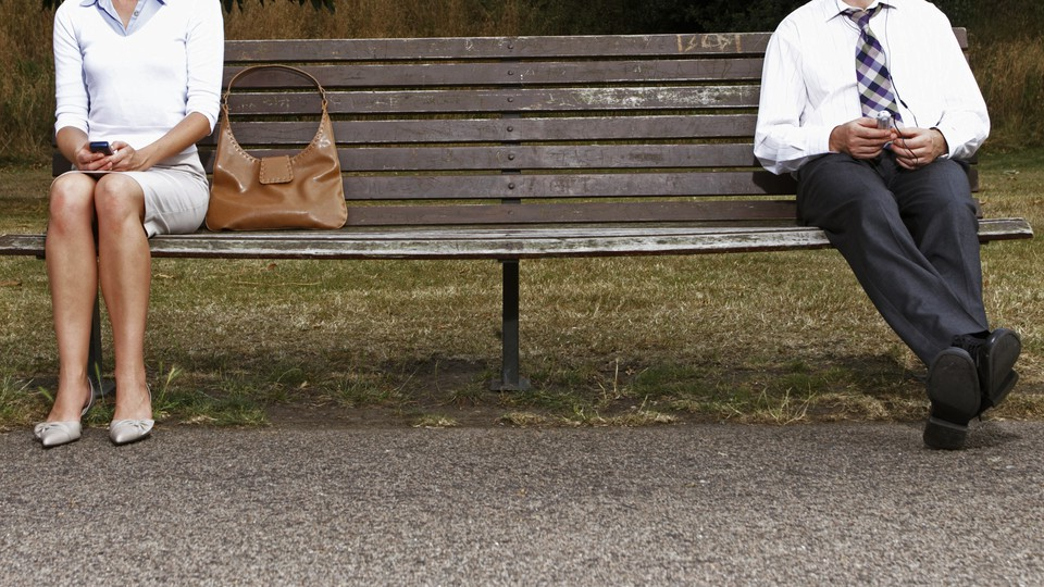 A woman and man sitting far apart on a bench