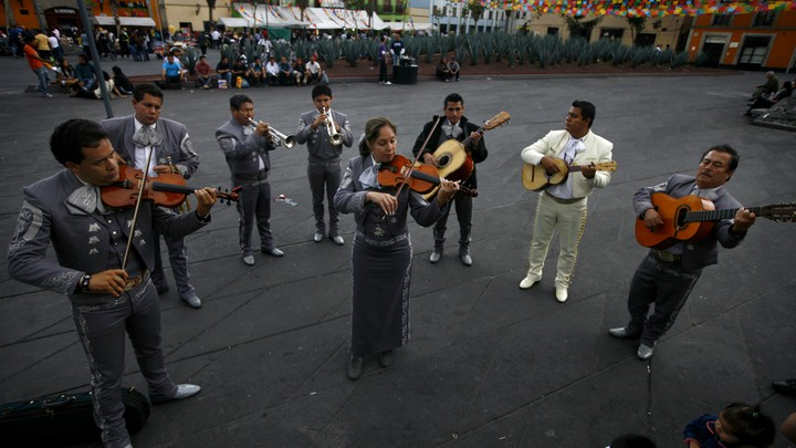 A mariachi band stands in a semi circle playing guitars, violins, and trumpets. A woman sands in the middle playing the violin.
