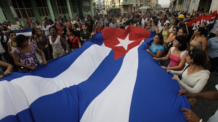 Pro-government youth carry a Cuban flag in front of the Ladies in White during a protest march in Havana on March 25, 2010.