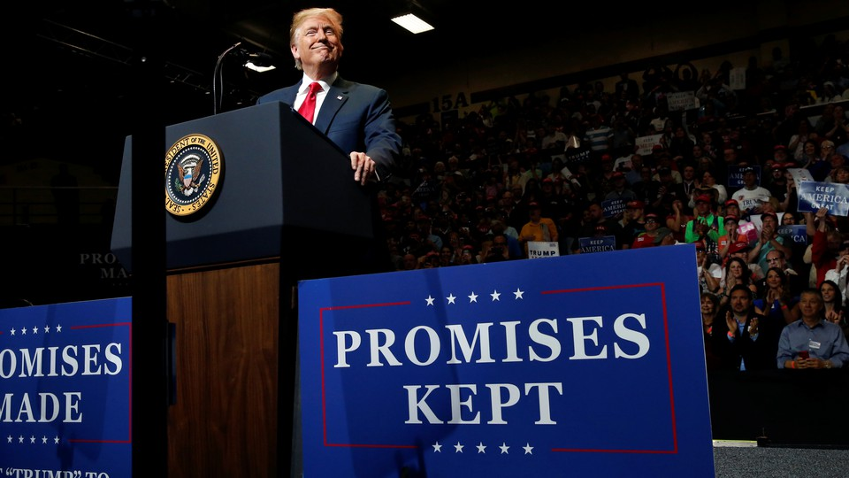 President Donald Trump stands at a lectern during a campaign rally.