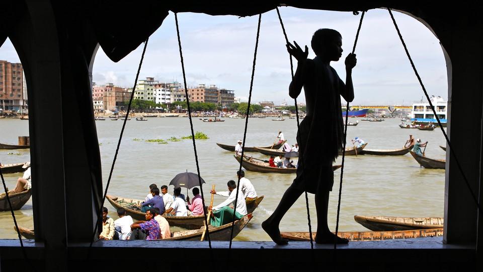 A boy walks along the side of a passenger ferry docked near Dhaka, Bangladesh.