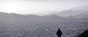 A man walks his dog on a hilltop overlooking San Francisco in the early morning hours on Mount Davidson.