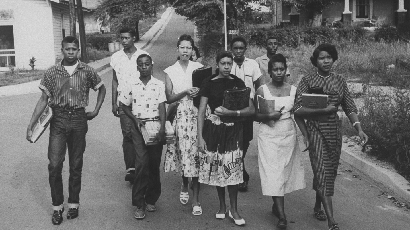 Jo Ann Allen Boyce and nine other Black students walk together down an empty road on their first day of desegregating Clinton High School in Clinton, Tennessee.