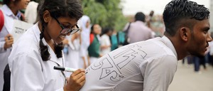 In Dhaka, a protester writes a slogan on another one's shirt during demonstrations over the death of two students in a traffic accident.