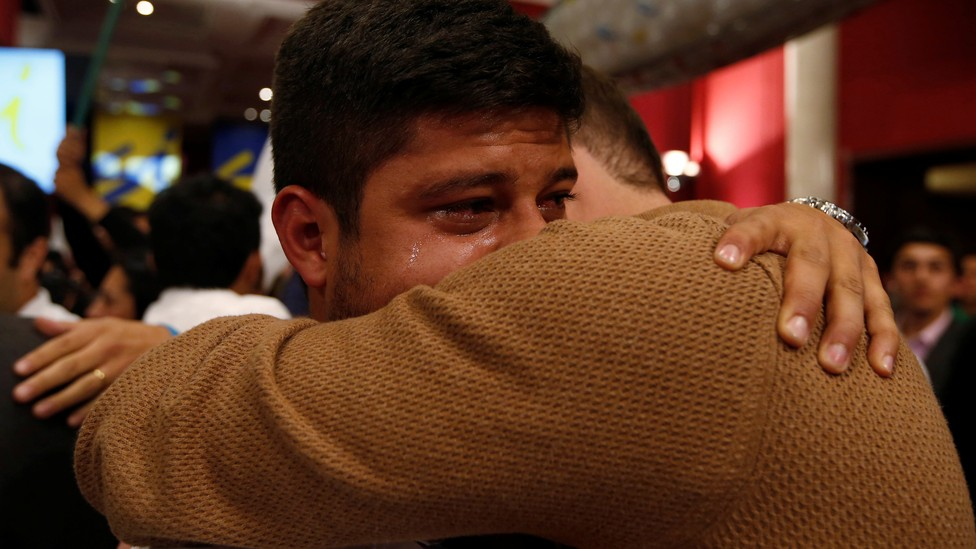 """Two men hug and cry after the nation votes """"no"""" on the recent FARC referendum."""