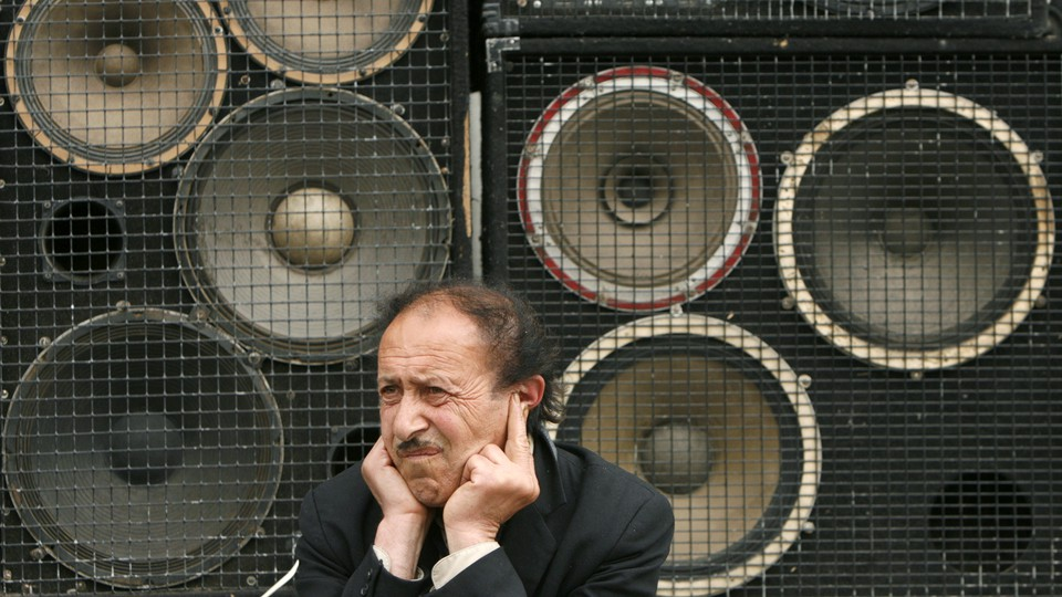 A man protects his ears as he sits in front of loudspeakers in central Yerevan in 2007.