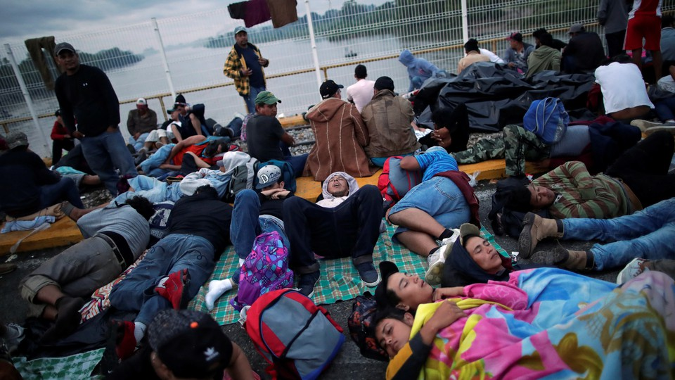 Honduran migrants, part of the caravan trying to reach the U.S., wait to open the gate on the bridge that connects Mexico and Guatemala on October 20, 2018