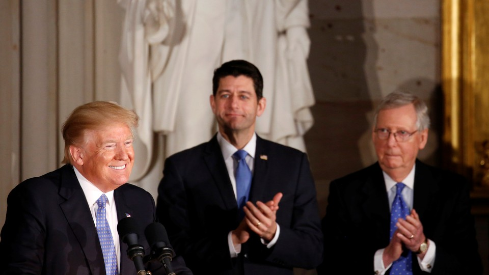 President Donald Trump smiling while Paul Ryan and Mitch McConnell clap