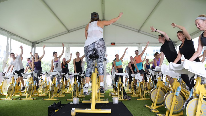 People ride yellow stationary bikes in an outdoor SoulCycle class.