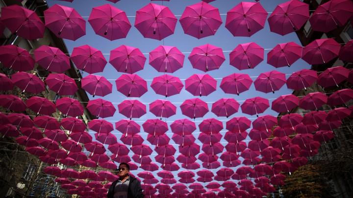 Pink umbrellas strung along a street