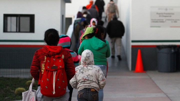 Immigrants from Central America and Mexican citizens prepare to cross into the U.S. to apply for asylum in Tijuana, Mexico.