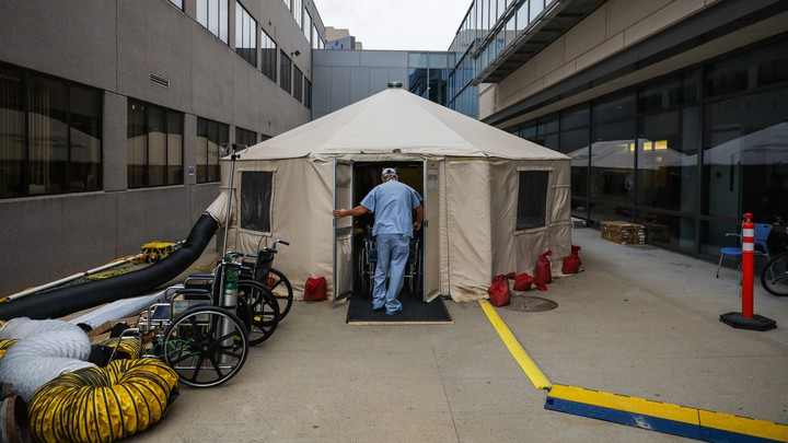 A doctor in front of a makeshift medical tent