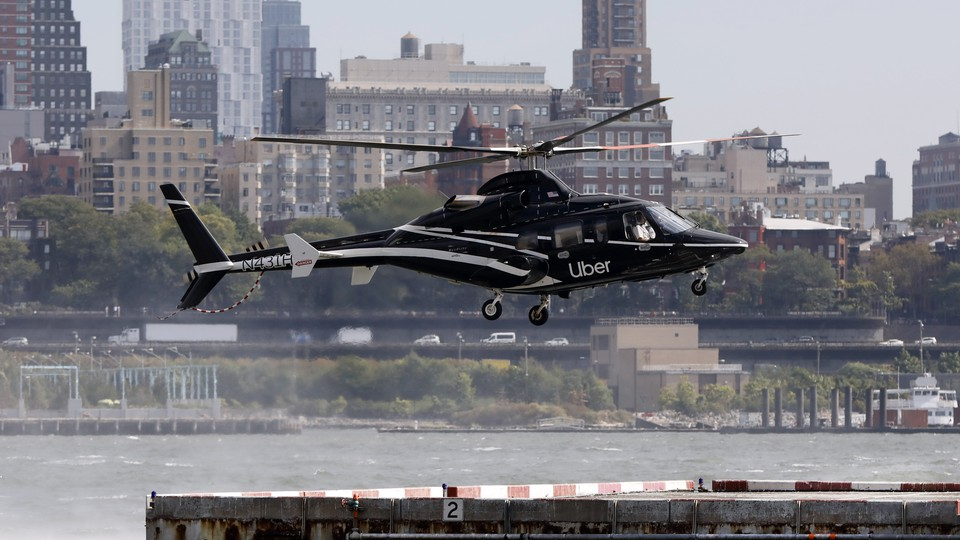 An Uber Copter lands at the Downtown Manhattan Heliport, in sight of buildings and the water.