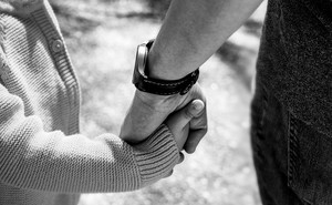 Black-and-white close-up image of an adult hand holding a child's hand