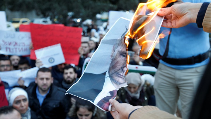 Protesters burn a picture of Vladimir Putin.