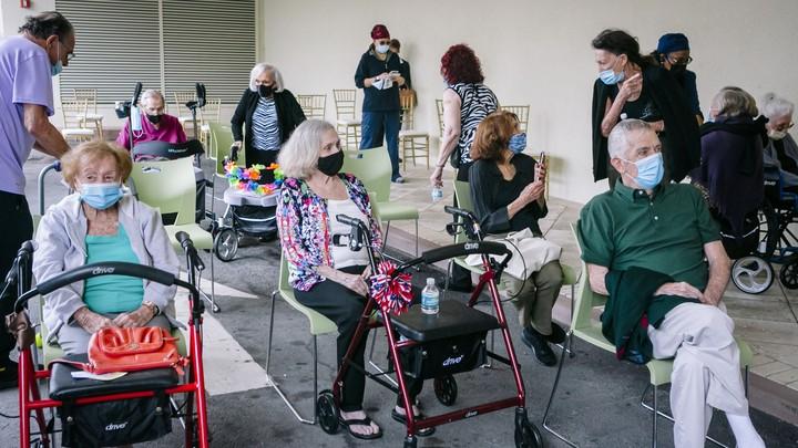 Seniors in masks wait for a coronavirus vaccine.