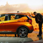 People examine a model EV in front of an image of rock formations