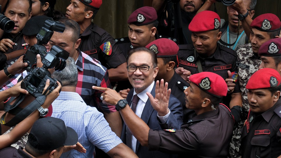 Anwar smiles and waves in between police officers and press photographers