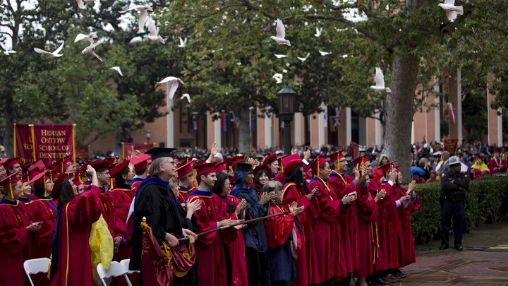 Doves fly over the heads of graduates dressed in deep red caps and gowns.