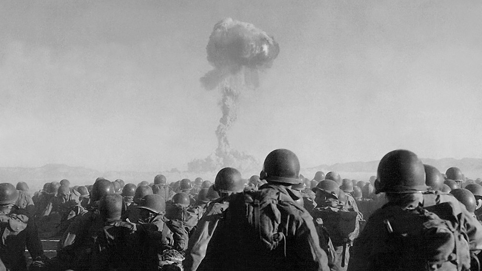 A group of troops watch a plume of smoke rise in the sky.