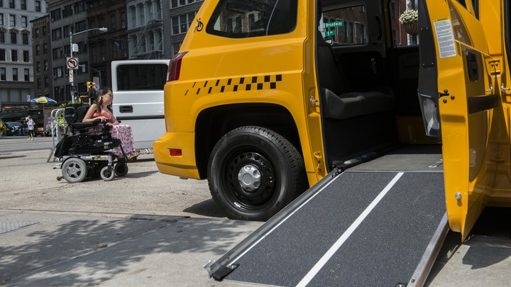 A woman in a wheelchair rolls past a taxi with an open ramp.