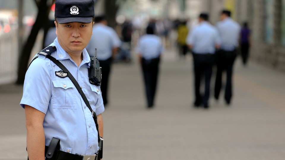 A policeman stands outside Beijing's Number 2 People's Intermediate Court Thursday during Xia Lin sentence hearing.