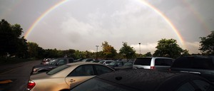 a photo of a full parking lot with a double rainbow over it
