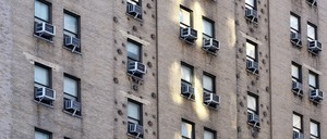 The facade of a building in Manhattan, with an A/C unit in every window.