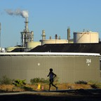 A jogger runs in front of the Phillips 66 refinery in the Wilmington neighborhood of Los Angeles.