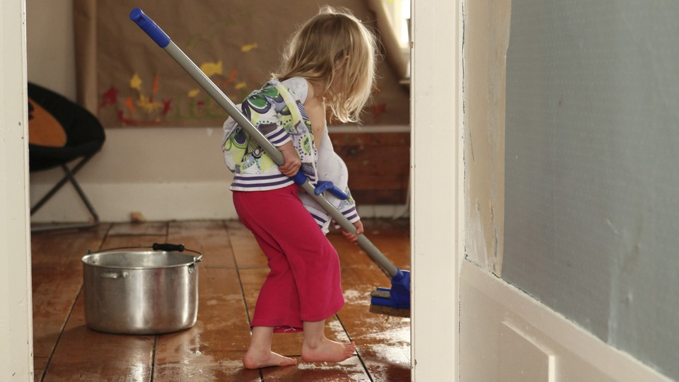 A child mops the floor