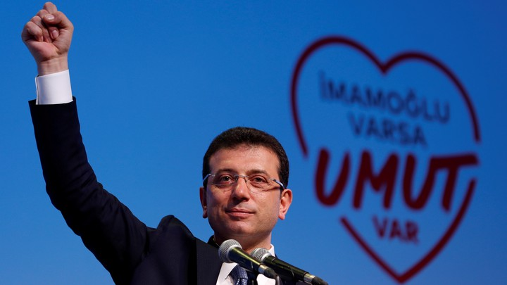 Ekrem İmamoğlu speaks at a rally with a heart graphic in the background.