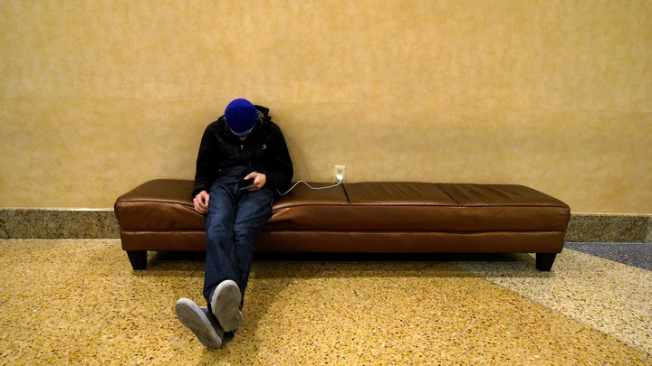 A man sleeps on a couch with his cell phone plugged into a nearby outlet