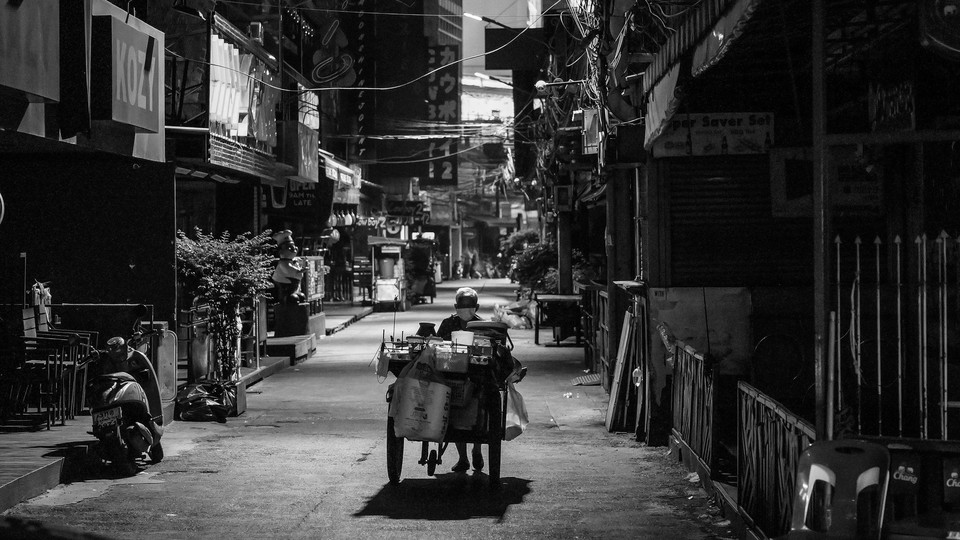 A woman pushes her food cart along an empty street in Bangkok