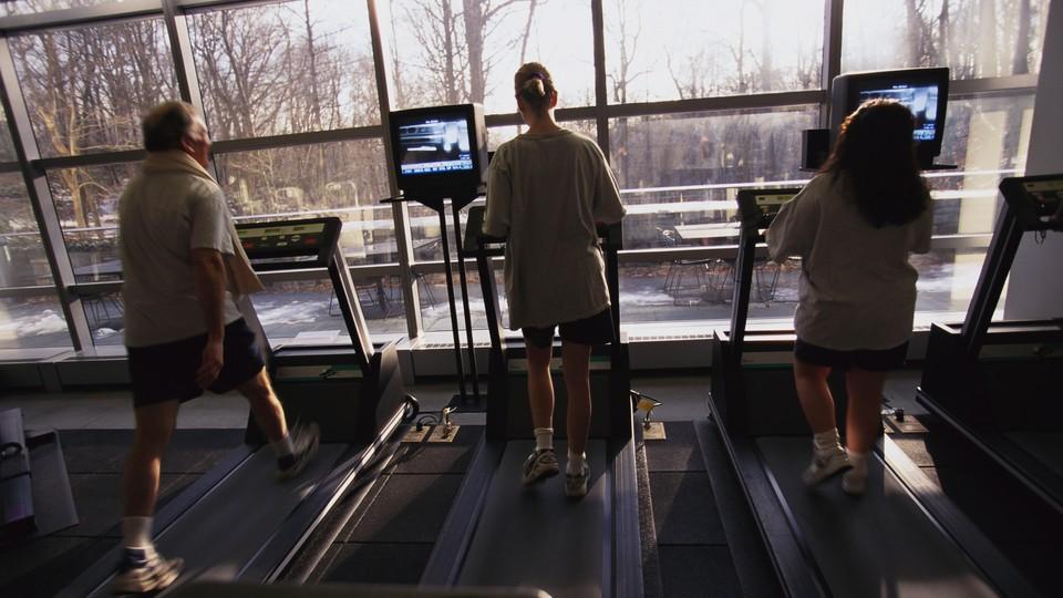 Three people run on treadmills.