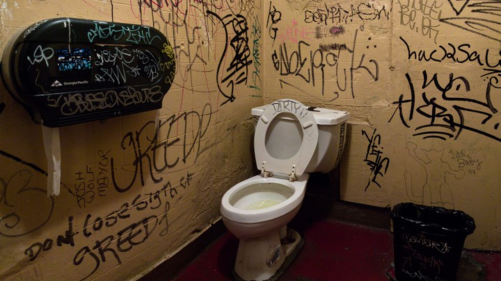 A dirty bathroom with graffiti on the walls