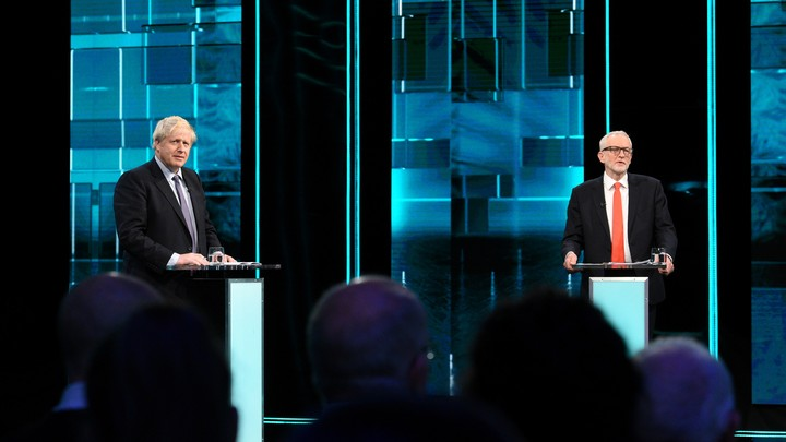 Boris Johnson and Jeremy Corbyn stand on a TV debate stage.