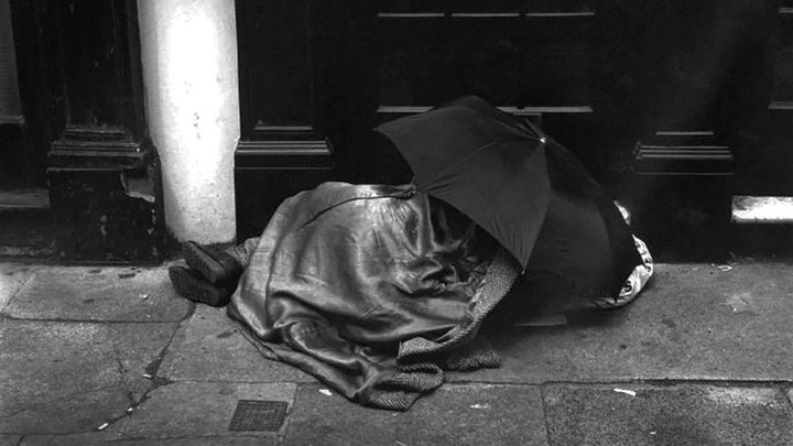 An unsheltered person sleeping under an umbrella in London