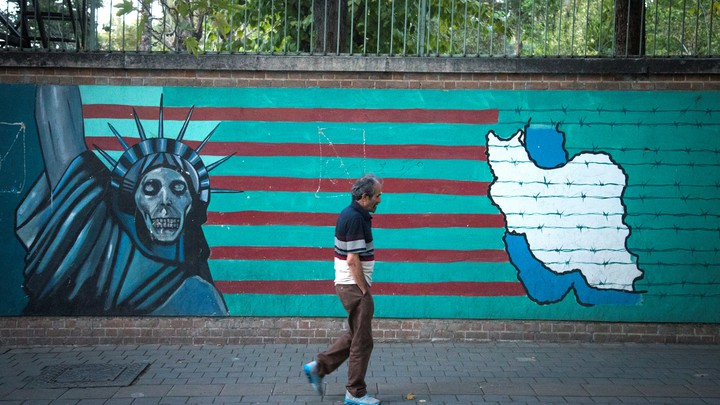 A man in front of an anti-U.S. mural featuring the Statue of Liberty, the American flag, and a map of Iran in barbed wire