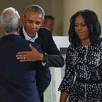 Barack Obama hugs Rahm Emanuel as Michelle Obama looks on.