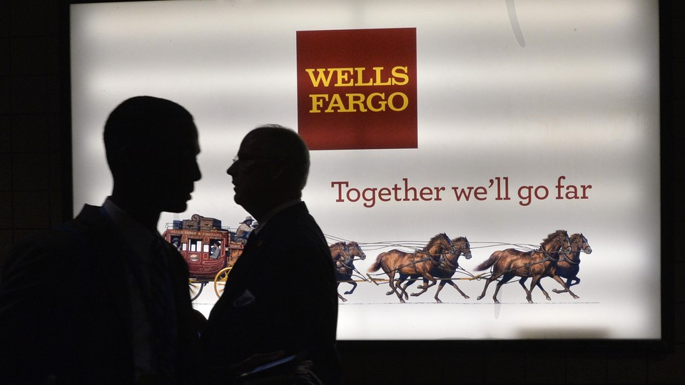 Patrons stand outside a Wells Fargo bank