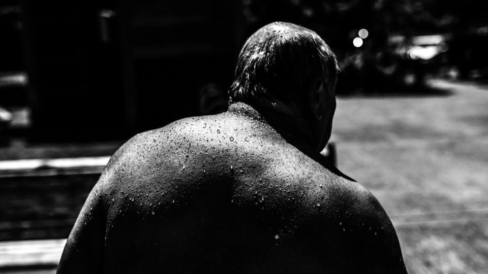 An older man, Pablo Miranda, sweats in the high heat in Portland.