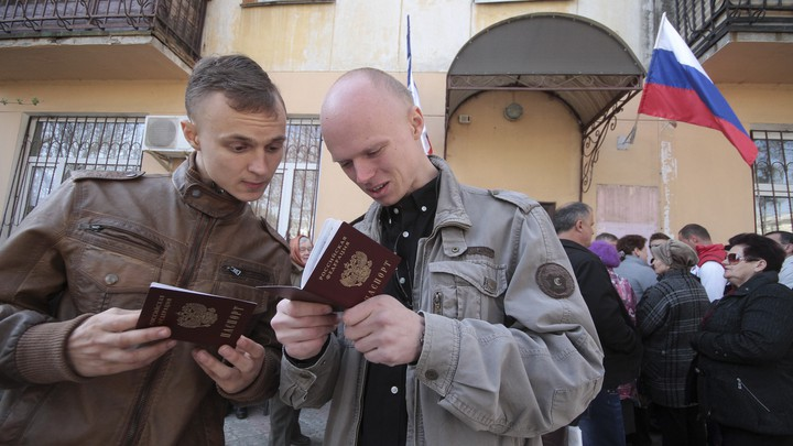 Men look at their new Russian passports after receiving them at a federal office in Simferopol, Crimea, in 2014.