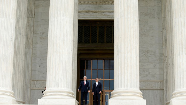 Justice Neil Gorsuch and Chief Justice John Roberts stand on the U.S. Supreme Court building steps in June.