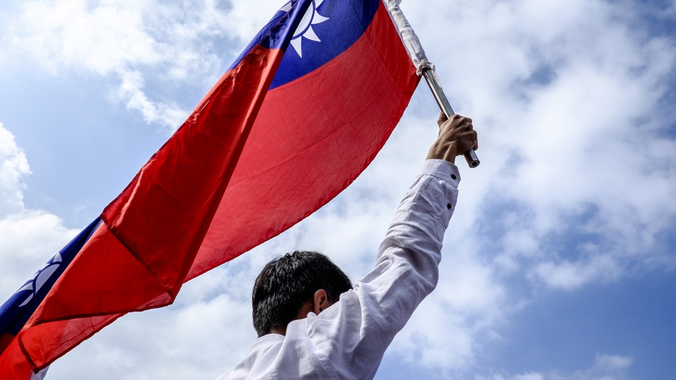 Man holding the Taiwan flag up in the air, in front of a blue sky